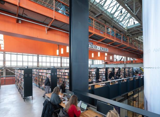 As áreas comuns são abertas ao público. Ali, qualquer um pode transitar pelas estantes recheadas de livros ou até mesmo trabalhar em balcões de estudo (Foto: Ossip Architectuurfotografie/ Arch Daily/ Reprodução)