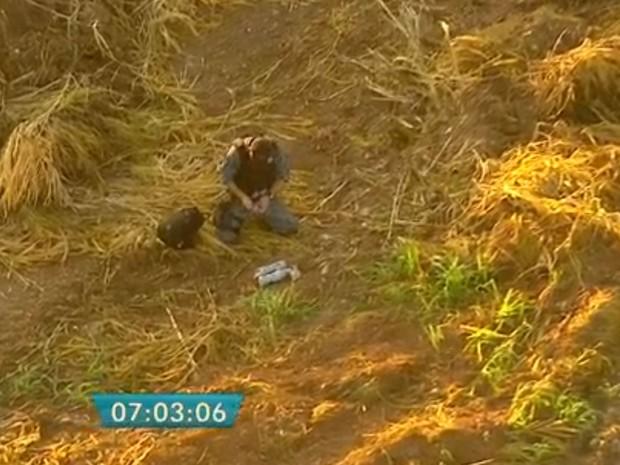 Policial do Gate leva material explosivo apreendido para ser detonado em um terreno baldio em Santo André (Foto: TV Globo/Reprodução)