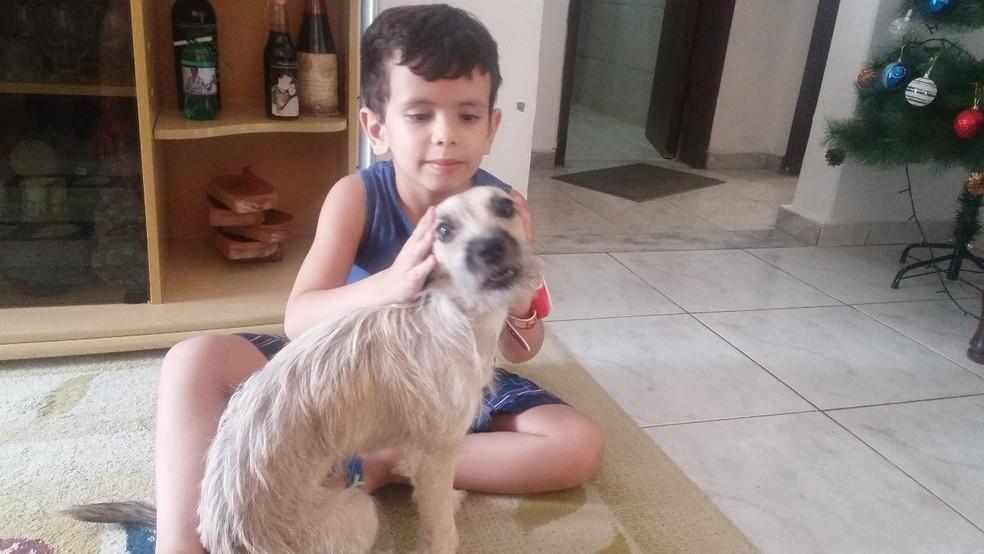 Mãe do Rodrigo adotou um cãozinho para estimular comunicação dele com o mundo (Foto: Tatiana Cândida Braga/ Arquivo pessoal)