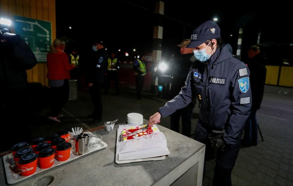 Policial estoniano serve bolo e café para comemorar reabertura da fronteira entre Estônia e Letônia nesta sexta-feira (15) — Foto: Ints Kalnins/Reuters