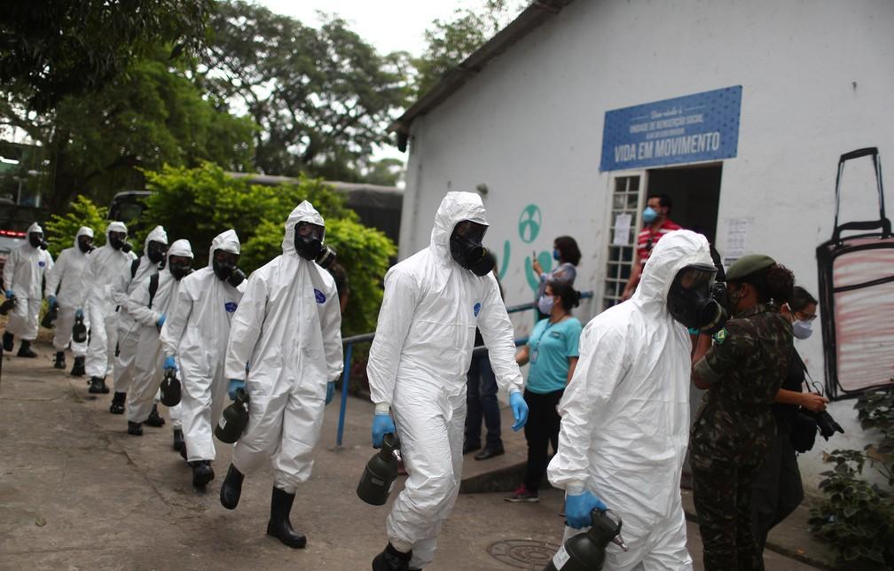 14 de maio - Oficiais do exército com equipamentos de proteção chegam para desinfetar o centro de acolhimento Stella Maris, em meio à pandemia de coronavírus (COVID-19), no Rio de Janeir — Foto: Pilar Olivares/Reuters