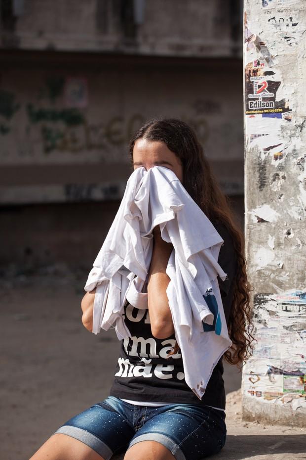 Bruna dos Santos com a blusa manchada de sangue que recebeu do Estado após a morte do filho (Foto: Daniela Dacorso)
