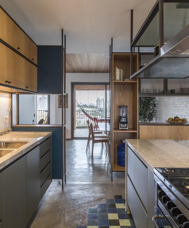 Na área da cozinha, um tapete de ladrilhos hidráulicos complementa o piso de cimento queimado. O ambiente tem marcenaria moderna (Ornare) que mantém o clima de integração com o restante do apartamento (Foto: Maira Acayaba/Divulgação)