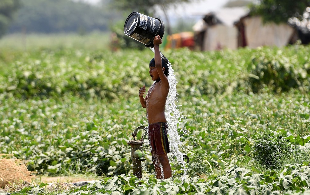 29 de maio - Menino toma banho de balde tentando refrescar-se durante dia quente em Nova Déli, na Índia — Foto: Money Sharma/AFP