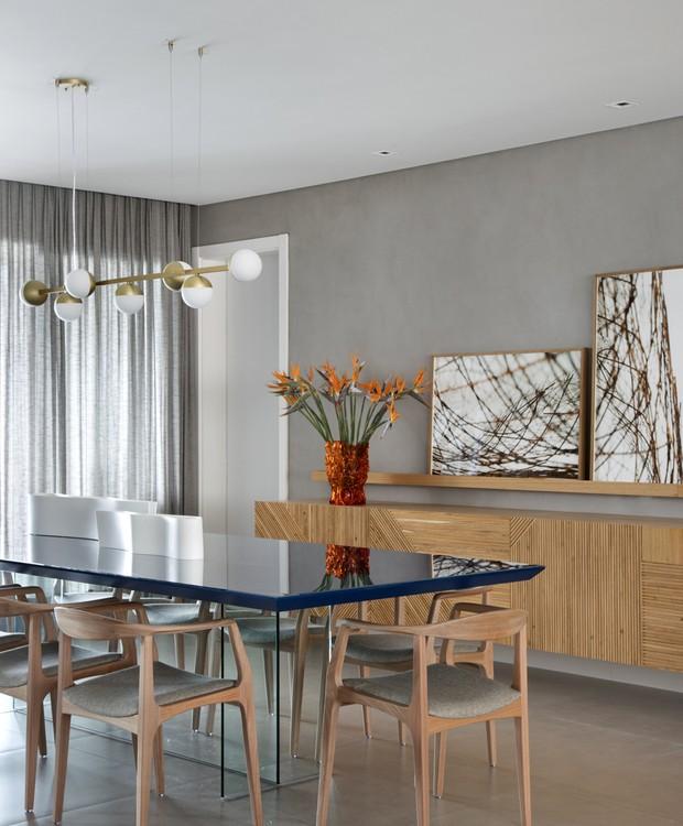 A mesa azul (Clami Design) teve a cor retirada da tela de Newton Mesquita. Cadeiras de Aristeu Pires e pendente Jabitucaba de Ana Neute (Foto: Denilson Machado/MCA Estúdio/Divulgação)