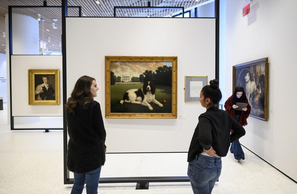 Mulheres observam quadro de cachorro no Museu Americano do Cachorro — Foto: Johannes EISELE / AFP