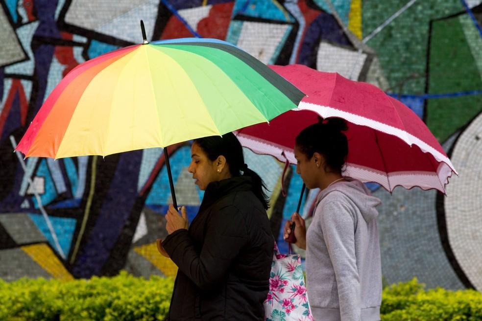 Pedestres andam sob chuva, nesta sexta (5), na Avenida São Luiz, região central da cidade — Foto: Dario Oliveira/Estadão Conteúdo