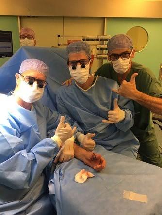 Médico comemoram o implante na mão esquerda do paciente