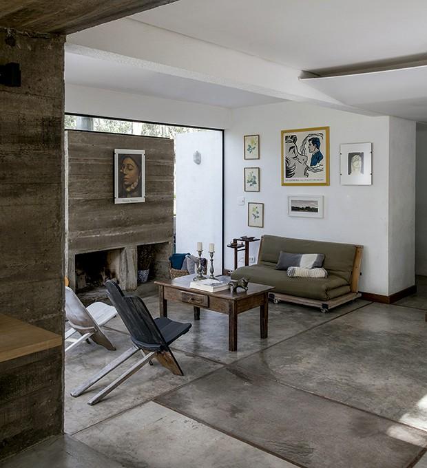 A gravura do artista pop Lichtenstein se destaca no ambiente onde há a lareira de concreto aparente. As cadeiras de madeira, montadas com duas peças de encaixe, foram trazidas do Rio Grande do Sul. Projeto do arquiteto Arthur Pugliese (Foto: Marco Antonio/ Editora Globo)