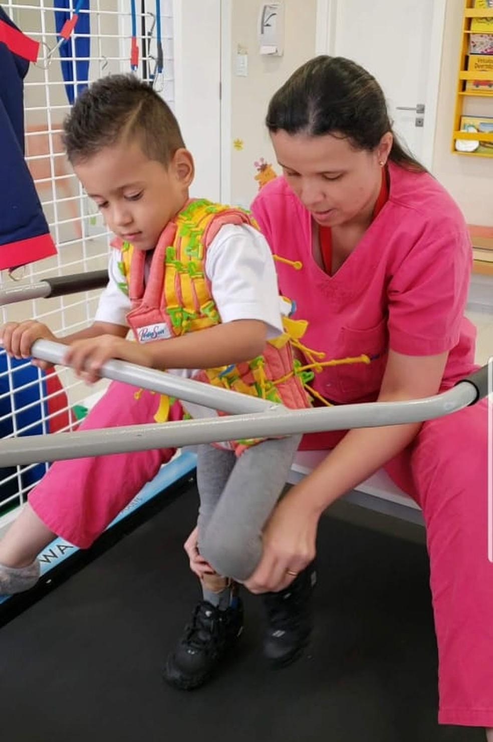 Dudu e a fisioterapeuta Caroline durante uma sessão do método PediaSuit — Foto: Arquivo Pessoal/Caroline Araujo