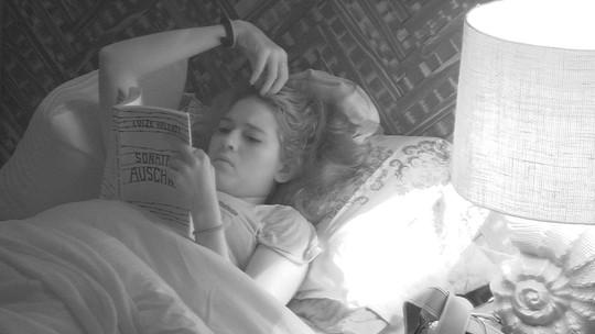 Ana Clara coça a cabeça enquanto lê no Bangalô do Líder