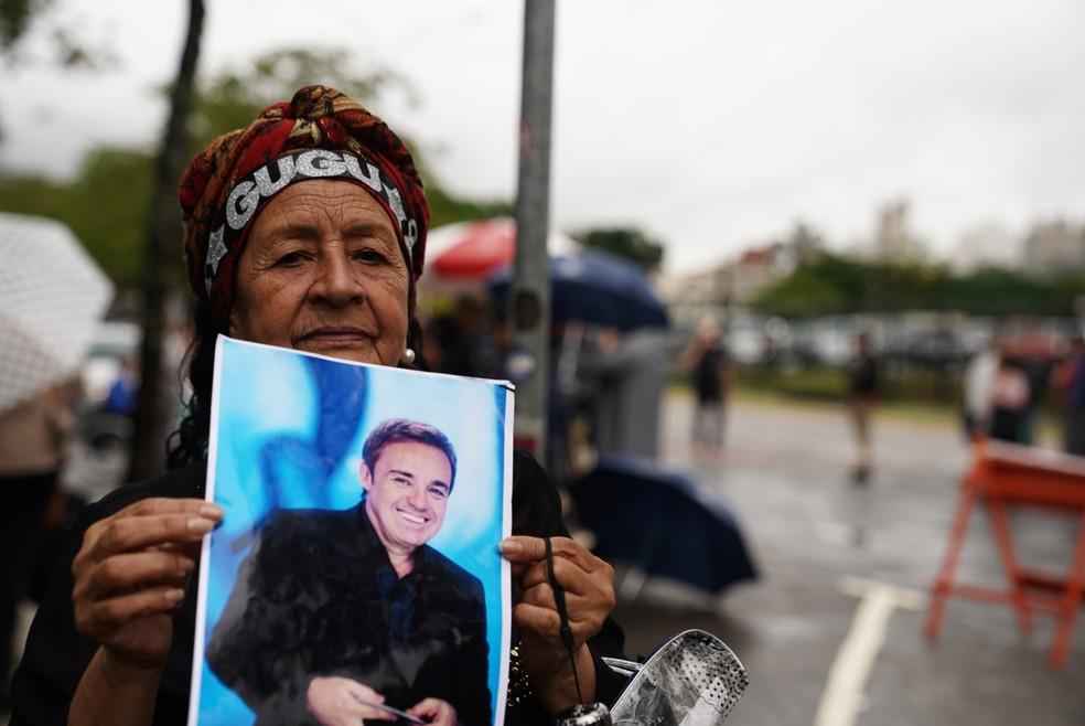 Fã segura imagem de Gugu Liberato na fila para participar de velório do apresentador na Alesp  — Foto: Marcelo Brandt/G1