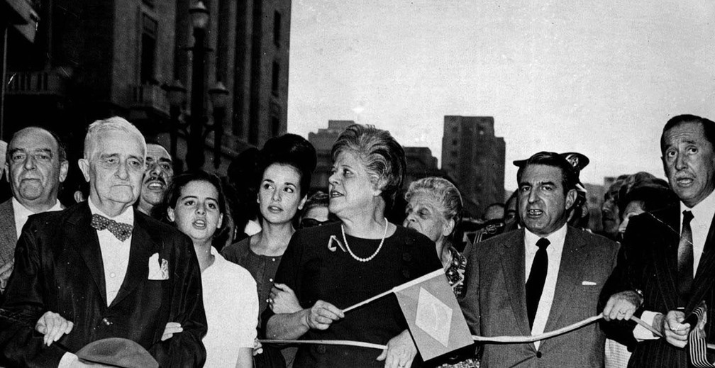 Leonor Barros (ao centro, com bandeirinha do Brasil), mulher de Adhemar de Barros, o deputado federal Cunha Bueno (de paletó cinza) e o deputado Herbert Levy (o último à direita) — Foto: Folhapress