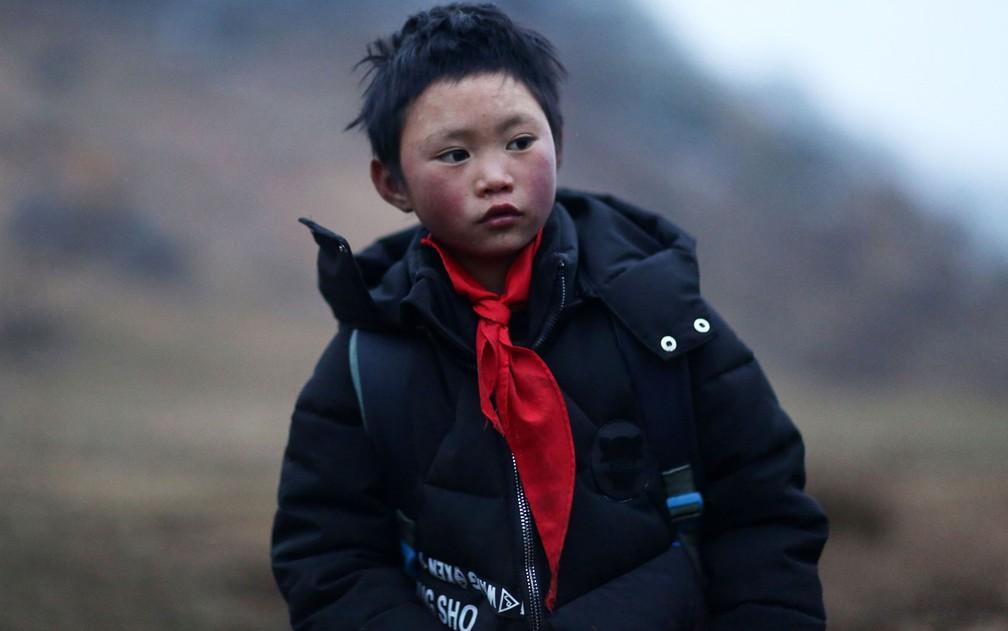 Apesar das mudanças no último ano, o sonho de Wang continua o mesmo: ele quer ser policial quando crescer — Foto: AFP