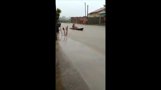 Morador anda de barco em rua alagada após chuva forte em MT; veja vídeo