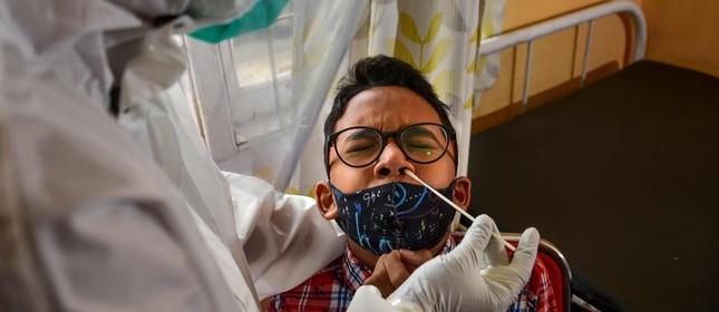 Menino faz teste swab para identificar se está infectado com o  novo coronavírus
