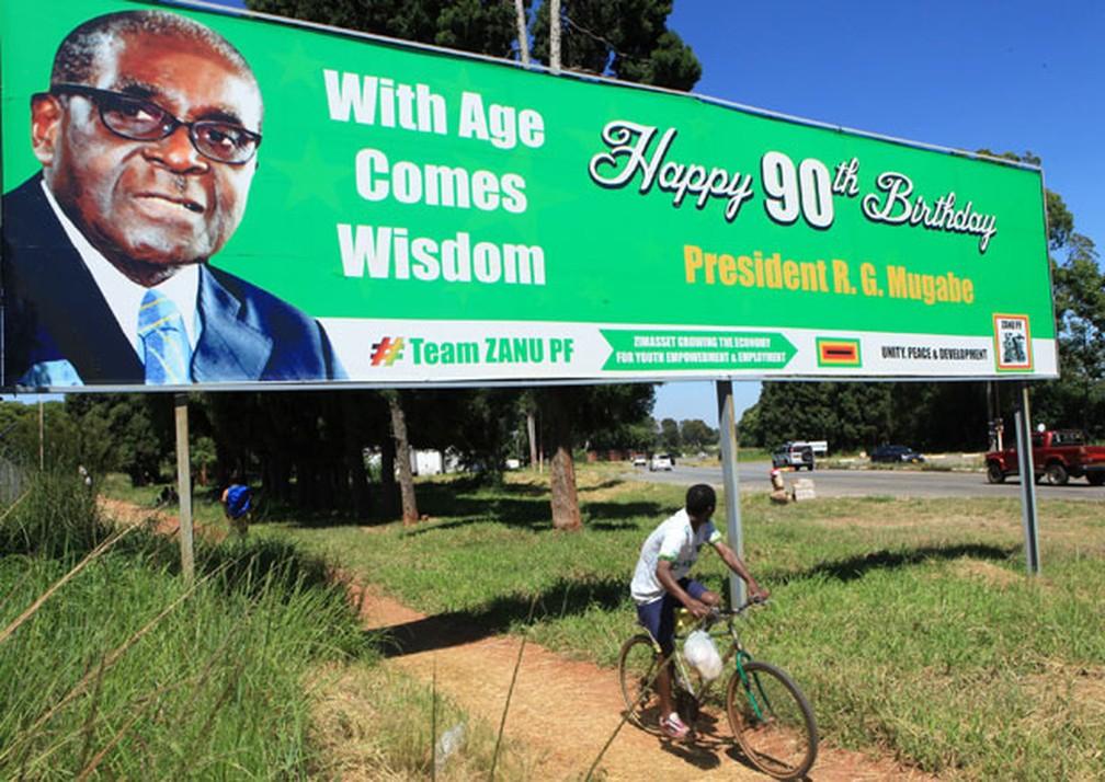Homem passa de bicicleta em frente a outdoor de aniversário dos 90 anos de Robert Mugabe. — Foto: Tsvangirayi Mukwazhi / AP Photo