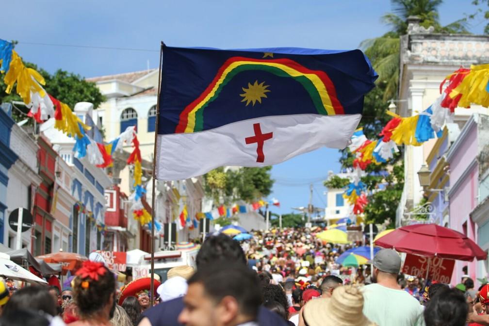 Bandeira de Pernambuco surge gigante entre foliões nas ladeiras de Olinda; símbolo vem da Revolução de 1817 (Foto: Marlon Costa/Pernambuco Press)
