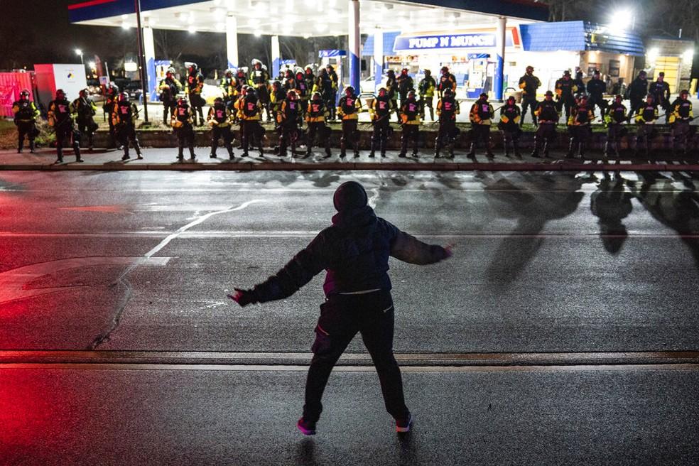 Manifestante se posiciona diante de barreira policial em Brooklyn Center na noite de segunda-feira (12) durante protesto contra morte de Daunte Wright — Foto: John Minchillo/AP Photo
