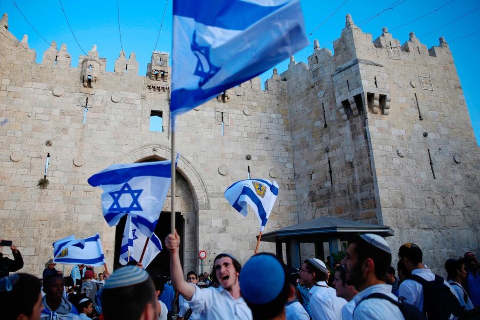 Imagem de 13 de maio mostra israelenses com bandeiras na Porta de Damasco, uma das entradas de Jerusalém antiga   (Foto: Ariel Schalit/ AP)