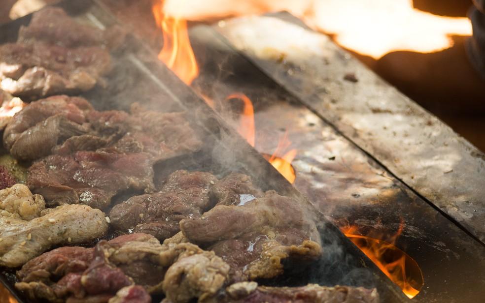 Churrasco é preparado em chapa de ferro durante a Queima do Alho. (Foto: Érico Andrade/G1)