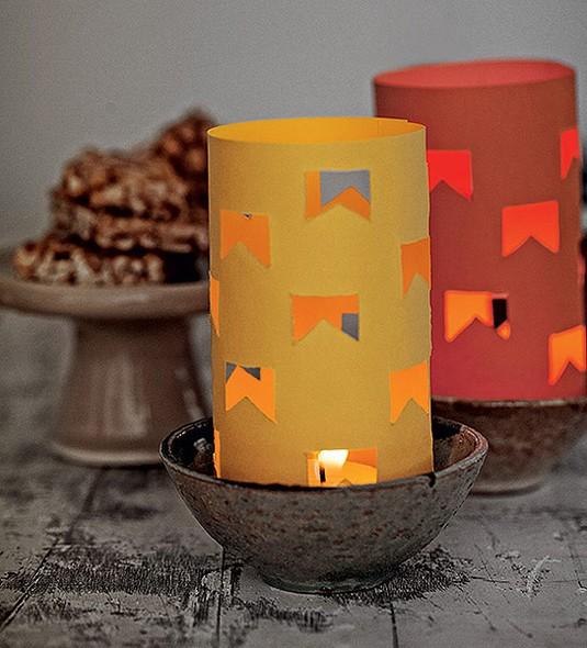 Lanterna, bandeirinhas, fogo: é praticamente um arraial portátil essa ideia para iluminar a mesa de quitutes juninos, feita com papel-cartão recortado com estilete e velinhas de réchaud