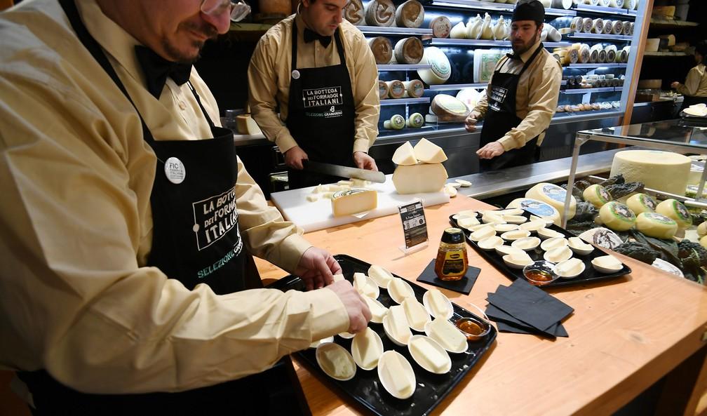 Vendedores apresentam diferentes tipos de queijo em estante do parque, em Bolonha (Foto: Vincenzo Pinto/AFP)