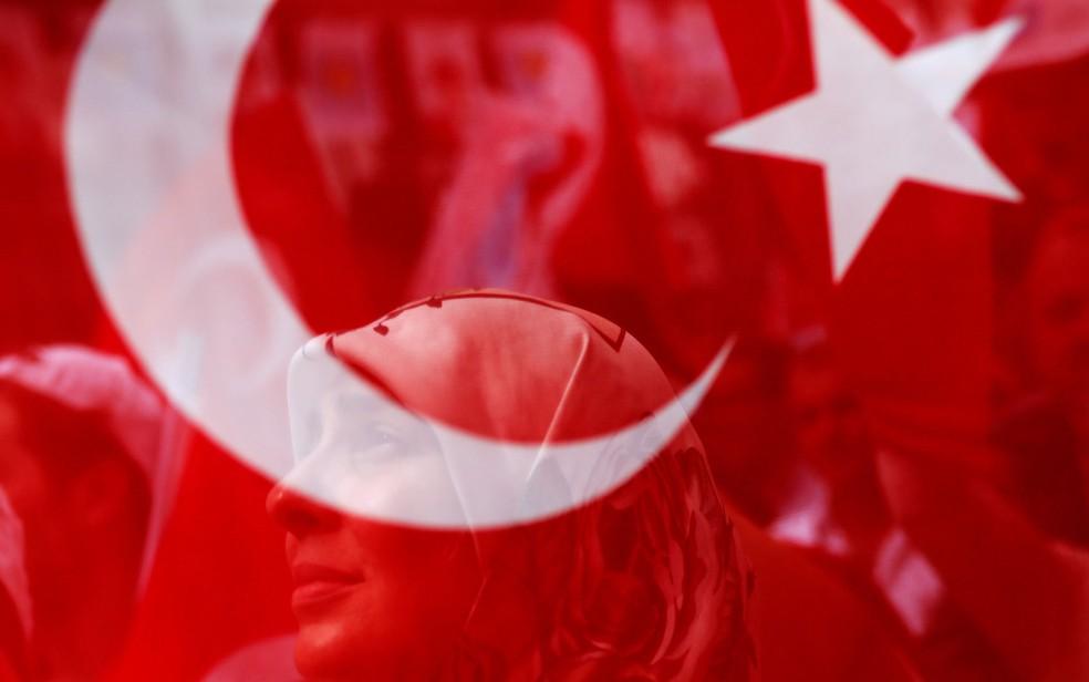 Mulher é vista através de bandeira turca em evento eleitoral em Istambul (Foto: Alkis Konstantinidis / Reuters)