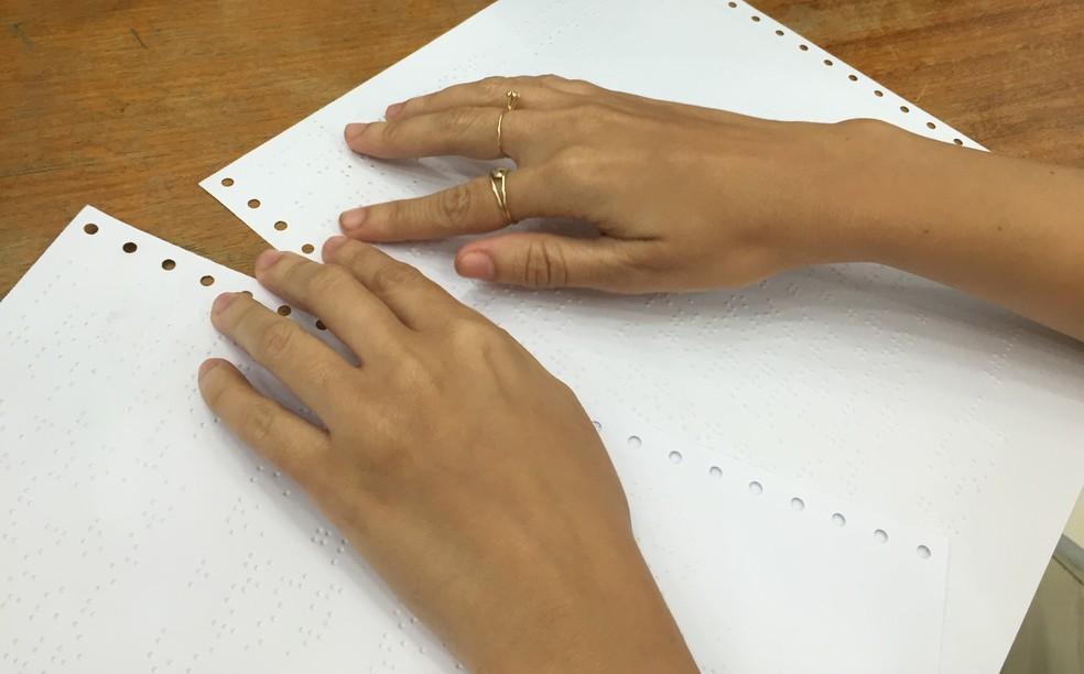 Mulher faz leitura de documento em braile — Foto: Inaê Brandão/G1