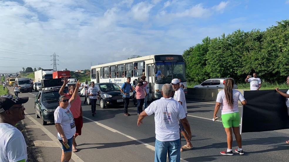As pessoas, que estão com faixas e cartazes, pedem melhoria e reivindicam atenção para a situação ambiental da Barragem Ipitang, que fica na região.  — Foto: Victor Silveira / TV Bahia