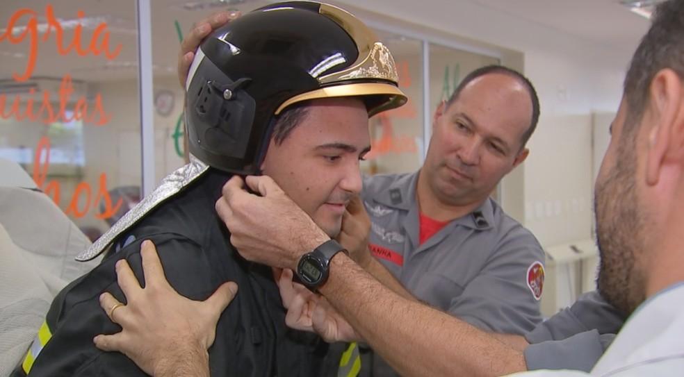 Luís coloca o capacete especial dos bombeiros (Foto: Reprodução/TV TEM)