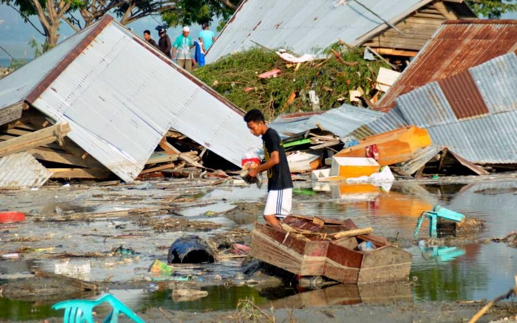 Homem observa danos causados pelo terremoto e tsunami em Palu, Sulawesi, na Indonésia — Foto: Rifki / AP Photo