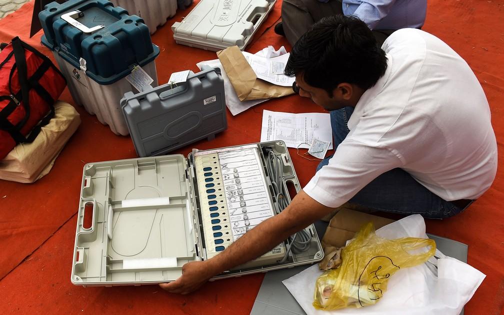 Funcionário da Comissão Eleitoral checa urna eletrônica e material de votação em centro de distribuição em Noida, na Índia, na quarta-feira (10) — Foto: Money Sharma/AFP