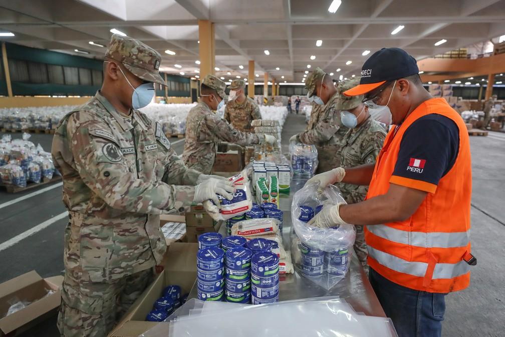 Militares peruanos embalam kits com alimentos e itens de higiene nesta quarta-feira (1º) — Foto: Luis Enrique Saldaña/Peruvian Ministry of Defense/AFP