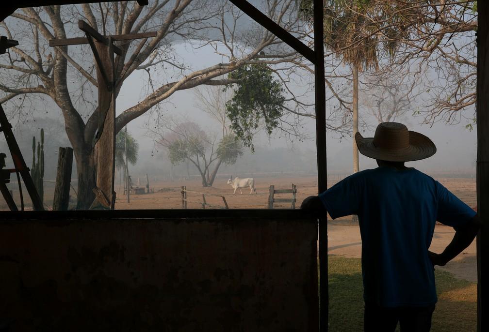 Dorvalino Conceição Camargo, de 56 anos, observa a fumaça que sobe no ar em uma fazenda em Poconé (MT) — Foto: Amanda Perobelli/Reuters