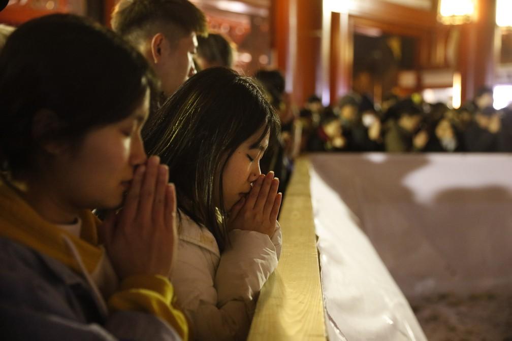 Pessoas rezam no templo Sensoji para celebrar o novo ano, em Tóquio, no Japão — Foto: Tatan Syuflana/AP Photo