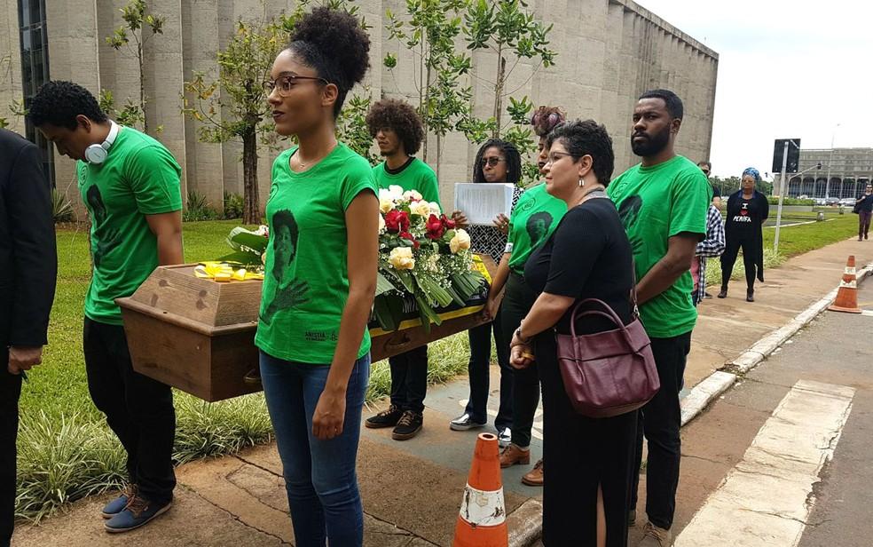 Representantes da Anistia Internacional carregam caixão em frente ao Ministério da Justiça em ato simbólico em defesa das vidas negras (Foto: Marina Oliveira/G1)
