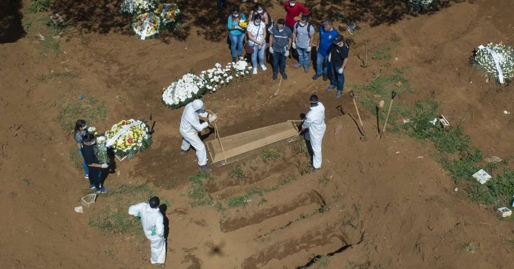 Coveiros usam equipamentos de proteção durante enterro no Cemitério da Vila Formosa, o maior da América Latina — Foto: André Penner/AP