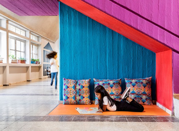 Debaixo da escada, um cantinho de leitura ganha almofadas grandes e estampadas, promovendo maior conforto (Foto:  Itay Benit/ Dezeen/ Reprodução)