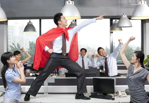 Funcionário com capa de superherói em cima de mesa (Foto: Lane Oatey/Blue Jean Images)
