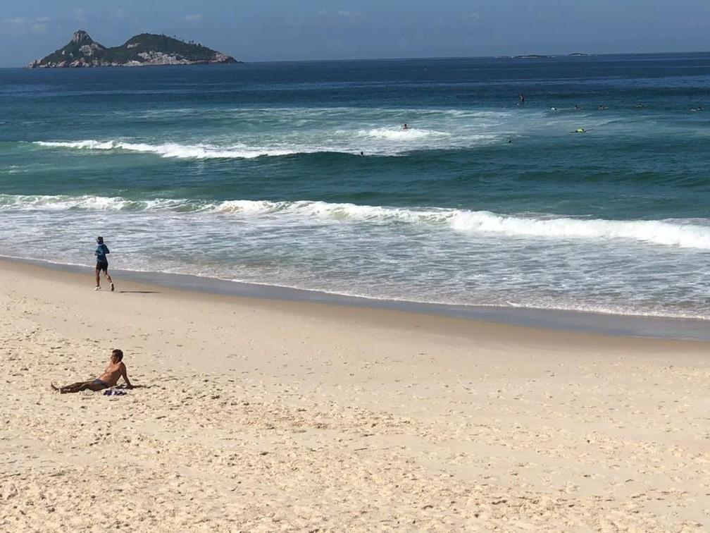 Na água, surfistas; na areia, homem toma sol e mulher se exercita — Foto: Henrique Coelho/G1 Rio