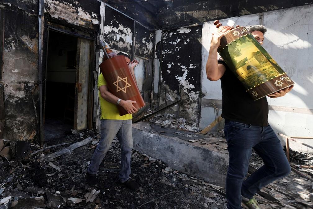 Os rolos da Torá, as escrituras sagradas judaicas, são removidos de uma sinagoga que foi incendiada durante confrontos violentos na cidade de Lod, em Israel, entre manifestantes árabes israelenses e a polícia em 12 de maio  — Foto: Ronen Zvulun/Reuters