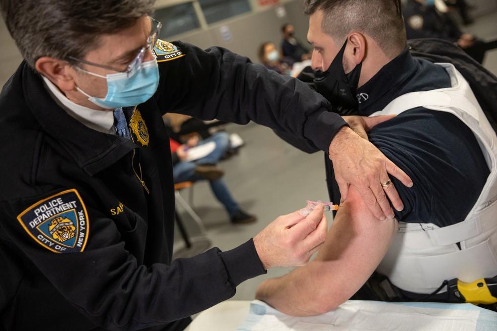 Agente do departamento de polícia de Nova York (NYPD) recebe dose da vacina contra a Covid-19 da farmacêutica Moderna Covid-19 na sede da academia da polícia no Queens, no subúrbio de NY, em 11 de janeiro de 2021 — Foto: Jeenah Moon/Pool via Reuters
