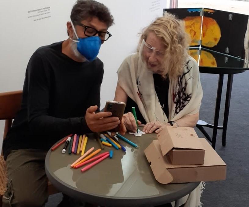 A artista Anna Bella Geiger, ao lado de um dos compradores,  desenha em forminha de brigadeiro ma Art Rio