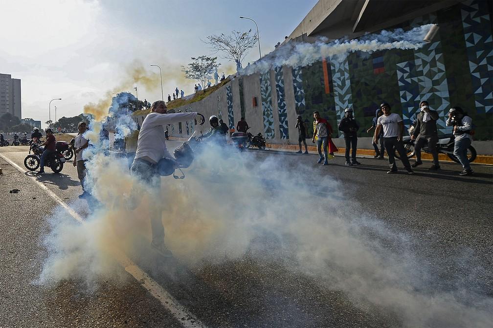 Manifestante apoiador de Guaidó atira de volta uma bomba de gás-lacrimogêneo atirada por forças de Maduro durante confronto em frente à base aérea 'La Carlota', em Caracas — Foto: Matias Delacroix/AFP