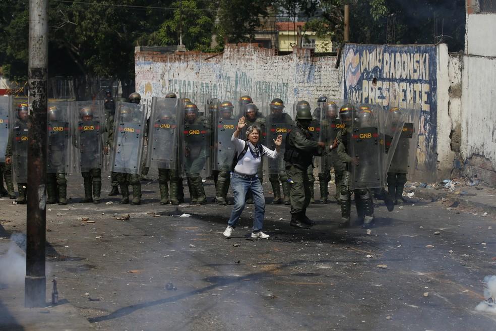 Um manifestante tenta deter a violência ao se apresentar diante de soldados em Ureña, na fronteira entre a Venezuela e a Colômbia — Foto: Fernando Llano/AP