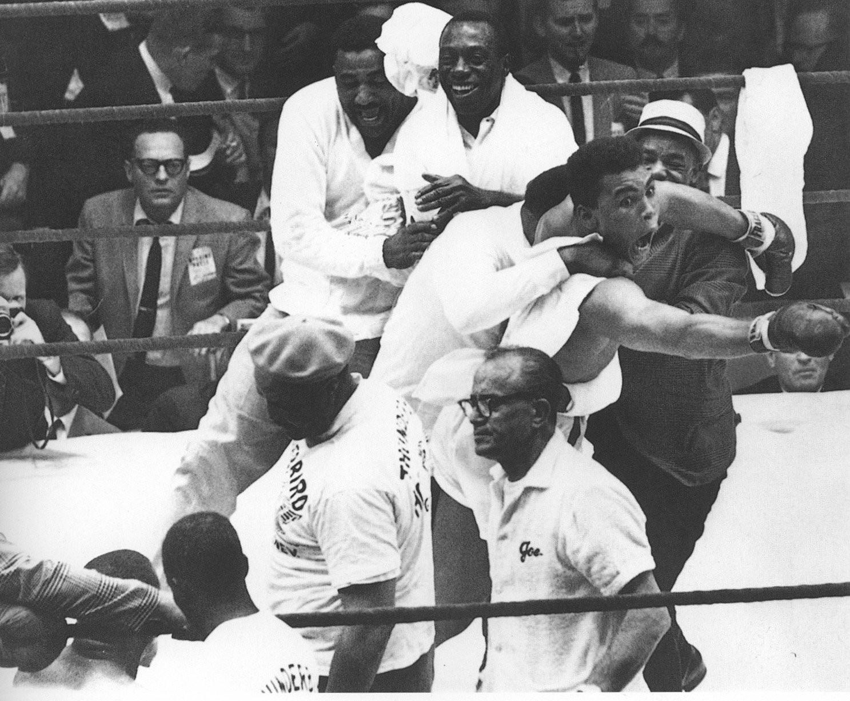 Muhammad Ali comemora a vitória no ringue com sua equipe