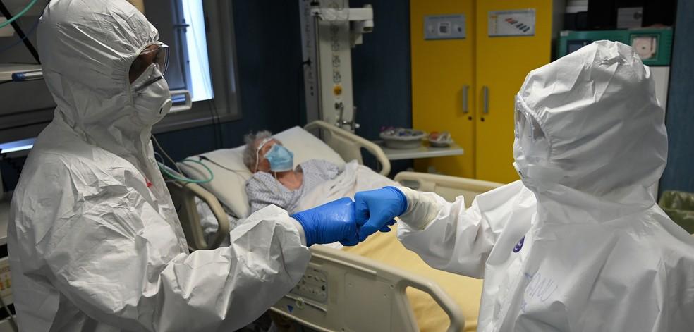 Médico e enfermeira se cumprimentam com as mãos em UTI em um hospital de Roma, na Itália, no dia 20 de abril. — Foto: Alberto Pizzoli / AFP Photo