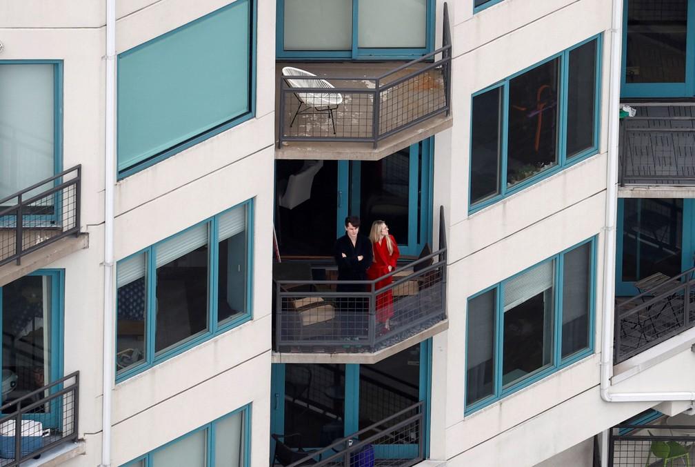 Um casal é visto na varanda do seu prédio em Nova Jersey, nos EUA, durante isolamento para evitar a propagação do novo coronavírus, em 30 de março — Foto:  Mike Segar/Reuters