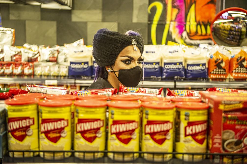 Maquiada e com adereços, funcionária de boate em Lima, no Peru, trabalha no espaço transformado em supermercado — Foto: Ernesto Benavides/AFP
